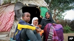 Ubah Mohamed Abdullahi, 33, right, sits with her son Abdullahi Yusuf Ahmed, 8, left, and daughter Neshad Yusuf Ahmed, 5, outside her hut in the Shedder refugee camp in far eastern Ethiopia.