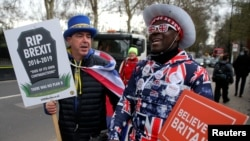 FILE - A pro-Brexit protester stands with anti-Brexit campaigner Steve Bray outside the Houses of Parliament in London, March 13, 2019.
