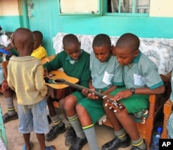 Children at the Divine Providence Children's Home in Kakamega, Kenya, examine a guitar.