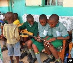 Children at the Divine Providence Children's Home in Kakamega, Kenya, examine a guitar.