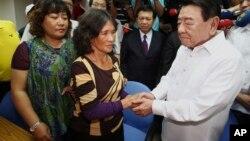 Chủ tịch Phòng Kinh tế và Văn hóa của Philippines ở Đài Loan (phải) xin lỗi thân nhân của ngư dân bị sĩ quan tuần duyên của Philippines bắn chết hồi tháng năm, 8/8/13