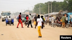 South Sudanese residents walk along a street of Bor, in Jonglei state. Around 1 million children in South Sudan have been forced to flee their homes since conflict erupted a year ago, Dec. 10, 2014.