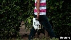 Un hombre lleva los zapatos de su hijo, luego de identificarlo como una de las siete víctimas de un tiroteo en una fiesta de graduación en Acajutla, El Salvador. Foto de Archivo. La tasa de homicidios en 2015, superó la de todos los países de Centroamérica en 16 años.