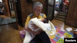 """Pastor Korea Selatan, Lee Jong-rak menggendong seorang bayi laki-laki yang dibuang dan mendoakannya di gereja Joosarang di Seoul (Foto: dok). Pastor Lee menyediakan """"baby box"""" untuk menampung bayi-bayi yang tidak diinginkan oleh para ibu di Nangok, Seoul."""