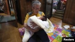 Seorang kakek menggendong bayi di gereja Joosarang di Seoul, Korea Selatan.