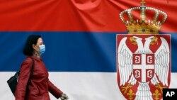 Žena sa maskom na licu hoda pored državne zastave Republike Srbije pre početka zabrane kretanja, tokom vanrednog stanja zbog epidemije koronavirusa u Srbiji (AP Photo/Darko Vojinović)