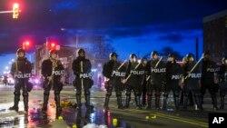 Polisi berjaga-jaga setelah perusuh beraksi di Baltimore (27/4).