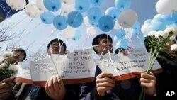 한국 서울역 광장에서 25일 천암함 사건 5주기를 하루 앞두고 추모 행사가 열렸다. 청년단체 회원들이 추모 메시지가 적힌 천안함 모양의 엽서를 들고 묵념을 하고 있다.