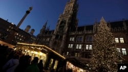 Visitors take a stroll at the Christmas market in front of the town hall at the Marienplatz square in Munich, Germany, Dec. 8, 2016. A strong police presence was felt at the square following the Berlin market attack.