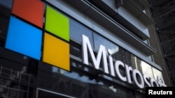 FILE - A Microsoft logo is seen on an office building in New York City in this July 28, 2015 file photo. Microsoft Corp announced more big cuts to its smartphone business on Wednesday.