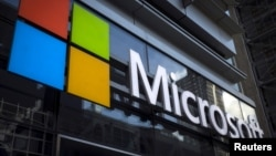 FILE - A Microsoft logo is seen on an office building in New York City in this July 28, 2015 photo. Microsoft Corp announced more big cuts to its smartphone business on Wednesday.