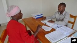 A lawyer gives legal advice to his client inside the USAID-funded Gisenyi Legal Aid Clinic in Rwanda.