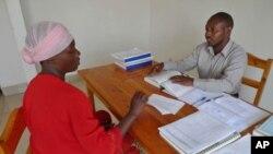 Lawyer Pascal Dusengeyeru gives legal advice to his client, Bernadine Nyiramugisha, inside the USAID-funded Gisenyi Legal Aid Clinic