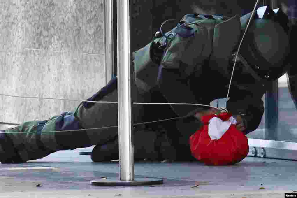 A bomb expert works on a package suspected to be a bomb, at the entrance of the Venezuela Central Bank in Caracas.
