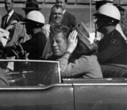 President Kennedy rides in a motorcade with his wife, Jacqueline, moments before he was shot and killed in Dallas, Texas, on November 22, 1963