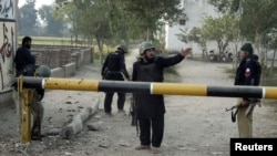 Pakistan security guards police station entrance after attack, Bannu, Dec. 10, 2012.