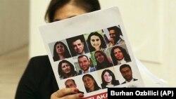 La députée pro-kurde du Parti démocrate populaire, Meral Danis Bestas, montre les photos de 12 législateurs emprisonnés de son parti, lors des débats au Parlement turc sur le projet de révision constitutionnelle pour renforcer les pouvoirs du président Recep Tayyip Erdogan, Ankara, Turquie, le lundi 9 janvier 2017.