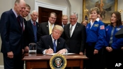 President Donald Trump signs a policy directive to send American astronauts back to the moon, and eventually Mars, in the Roosevelt Room of the White House, Dec. 11, 2017, in Washington.