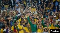 Pesepakbola Brazil merayakan kemenangan mereka di aatas podium, setelah memenangkan Piala Konfederasi melawan Spanyol di stadion Maracana di Rio de Janeiro (30/6).