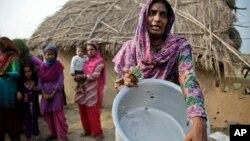 Žena u indijskom selu Džora Farm blizu granice s Pakistanom pokazuje navodne rupe od metaka u koritu