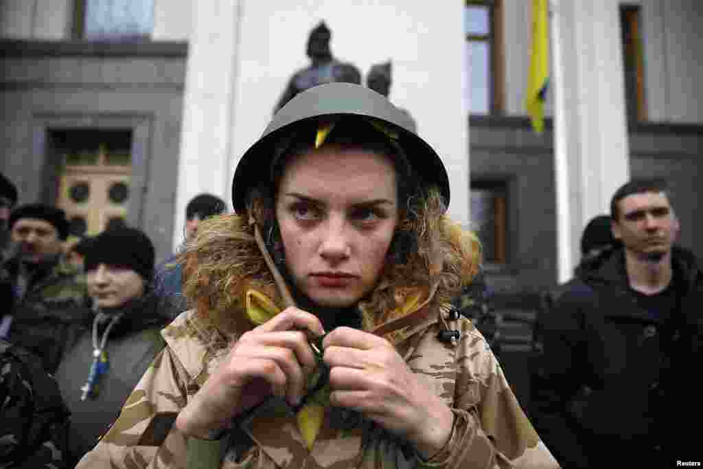 An anti-Yanukovych protester buckles her helmet as she stands guard outside the parliament building along with her comrades in Kyiv, Feb. 27, 2014.
