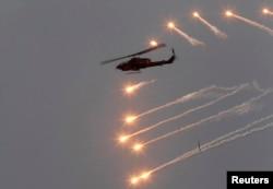 """2013年4月17日,台湾在澎湖一带举行""""汉光军事演习""""。图为一架AH-1W攻击直升机释放光束躲避敌方导弹。"""