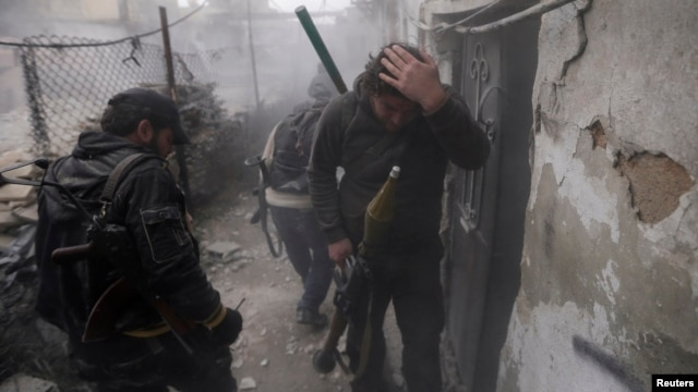 A Syrian rebel grabs his head as the smoke subsides, during fighting between the two sides in the Ain Tarma neighborhood of Damascus. Jan. 13, 2013