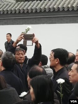 尽管当局规定不许自带鲜花,但仍有部分悼念者手持鲜花等候参加李昭告别仪式