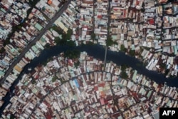 FILE - This aerial photo taken on October 19, 2018 shows houses along the Xuyen Tam canal in Ho Chi Minh City.