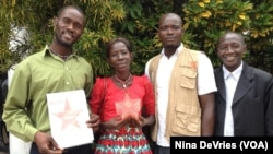 Maseray Kamara, flanked by her fellow burial team members in Freetown, holds the the Bond International Humanitarian Award, given to burial teams from across Sierra Leone for their contributions to stopping the spread of the Ebola virus, June 5, 2015.