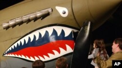 FILE - A man gives his daughter a close-up look at a Flying Tiger fighter plane at the U.S. Air Force Museum in Dayton, Ohio. Richard Sherman, who was a member of the Flying Tigers in World War II, died Jan. 9, 2019, at age 96 in Louisiana.