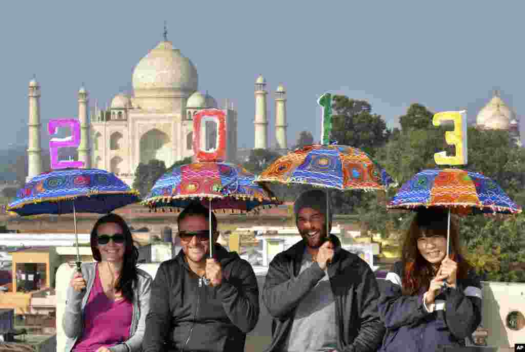 Tourists pose as they carry umbrellas with numbers to welcome the new year on the terrace of a hotel near the Taj Mahal in Agra, India, December 31, 2012.