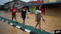Local residents walk on a road divider to avoid floodwaters in Kota Bahru, Dec. 28, 2014.
