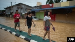 当地居民在洪水旁行走