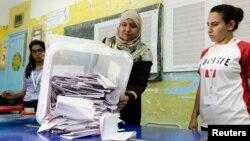 Petugas di Tunis menumpahkan kertas suara menyusul pemilu di Tunisia (26/10). (Reuters/Anis Mili)