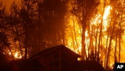 Un incendio forestal arde detrás de una casa en Twisp, estado de Washington, el miércoles, 19 de agosto de 2015.