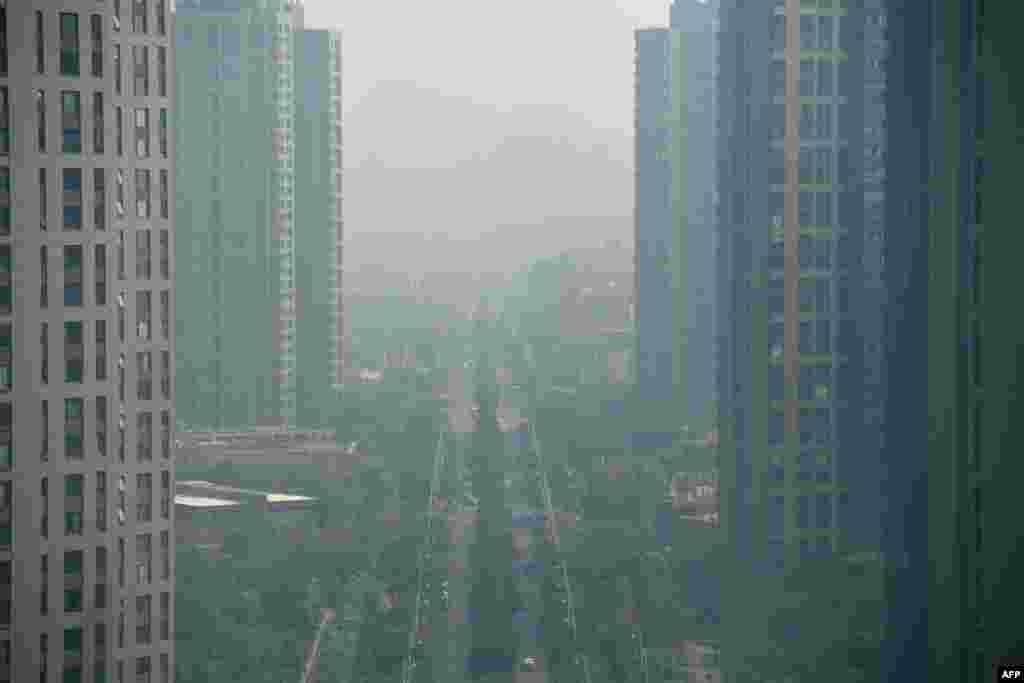 """2018年8月6日,江苏省南京市空气污染的一天,高楼、绿树、公路、汽车都在雾霾中。南京《交汇点》8月14日报道说,臭氧污染""""大有取代PM2.5之势,成为影响空气质量的最大污染物之一,近五年来,臭氧一直笼罩在南京城上空,最近三年,臭氧超标均超过50天。 """""""