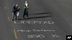 Manifestantes antigubernamentales caminan ante un mensaje en el que invocan el artículo 350 de la Constitución que da derecho a rebelarse contra la injusticia.
