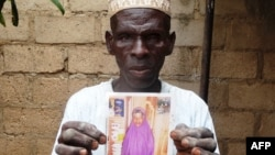 FILE - Sani Garba, 55, holds a picture of his then 14-year-old daughter-in-law Wasila Tasi'u, in Unguwar Yansoro, 63 kilometers north of Kano, Nigeria. Charges were dropped against the girl, now 14, who was accused of killing her 35-year-old husband.