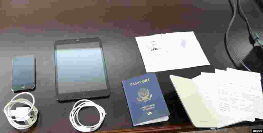 Personal possessions of U.S. citizen Matthew Todd Miller, including his passport and a ripped North Korean visa, are shown during his trial at the North Korean Supreme Court in this undated photo released by North Korea's Korean Central News Agency (KCNA), Pyongyang, Sept., 14, 2014.