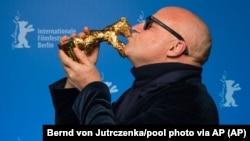 Gianfranco Rosi, directeur de 'Fuocomare', embrasse l'Ours d'or du meilleur film lors de la cérémonie de remise des prix 2016 au Festival de Berlin Berlinale le samedi 20 février 2016 à Berlin. (Bernd von Jutrczenka / pool photo via AP)