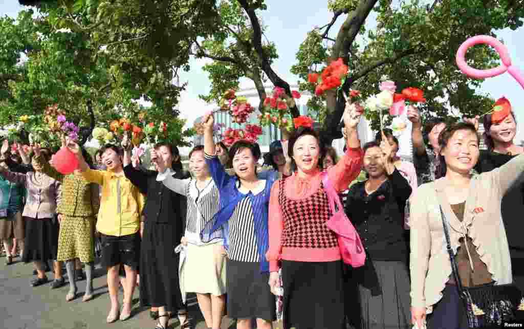 평양 주민들이 북한의 탄도미사일 '화성-12' 개발자들을 환영하며 꽃을 흔들고 있다.