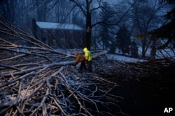 Streets department workers David Boardly, left, and James Ockimey clear a downed tree during a winter storm, March 2, 2018, in Marple Township, Pa.