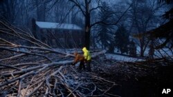 Streets department workers David Boardly, left, and James Ockimey clear a downed tree during a winter storm, March 2, 2018, in Marple Township, Pa. A nor'easter pounded the Atlantic coast with hurricane-force winds and sideways rain and snow Friday.