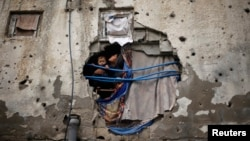 Palestinian children look out through a hole covered with a blanket in their family house, that witnesses said was damaged by Israeli shelling during a 50-day war last summer, in the east of Gaza City January 7, 2015. Heavy rains and near-freezing tempera