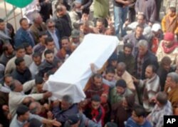 Mourners outside the Benghazi courthouse, seat of the rebel movement, carry the coffin of a victim of a munitions depot blast, March 5, 2011