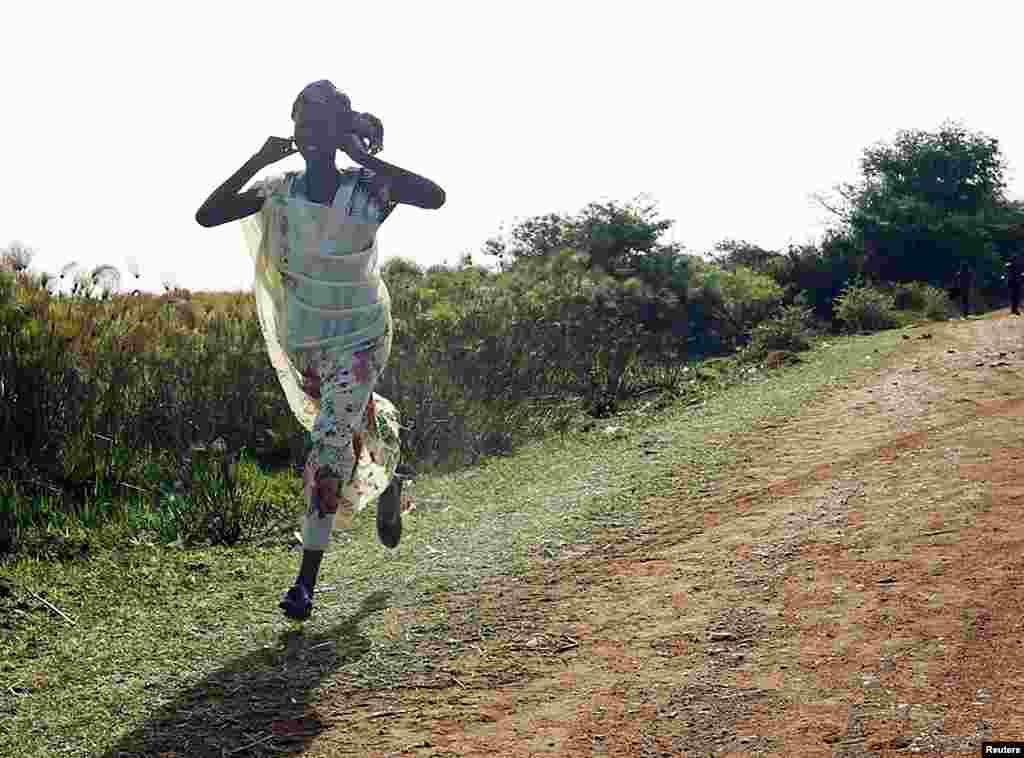 A woman runs along a road during an air strike by the Sudanese air force in Rubkona near Bentiu, South Sudan, April 23, 2012. (Reuters)