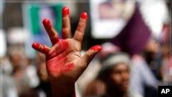 ຜູ້ປະທ້ວງຕໍ່ຕ້ານລັດຖະບານຄົນນຶ່ງ ຍົກມືທີ່ທາສີແດງຂຶ້ນ ທີ່ເປັນສັນລາລັກຂອງການນອງເລືອດ ໃນການປະທ້ວງ ບັ້ນນຶ່ງ ຮຽກຮ້ອງໃຫ້ປະທານາທິບໍດີຊາເລ ລາອອກ ທີ່ເມືອງ Taiz, ວັນທີ 1 ພະຈິກ 2011.