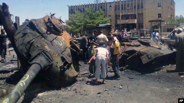 An image from Edlib News Network shows citizens looking at a Syrian tank destroyed during clashes between rebels and Syrian government forces in Idlib province, June 4, 2012. (The photo cannot be independently confirmed)