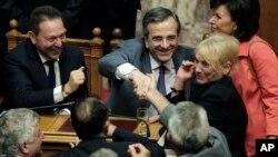 Menteri Keuangan Yunani Yannis Stournaras (kiri) dan PM Yunani Antonis Samaras (dua dari kiri) menerima ucapan selamat dari para pembuat kebijakan seusai sidang parlemen di Athena (18/7).